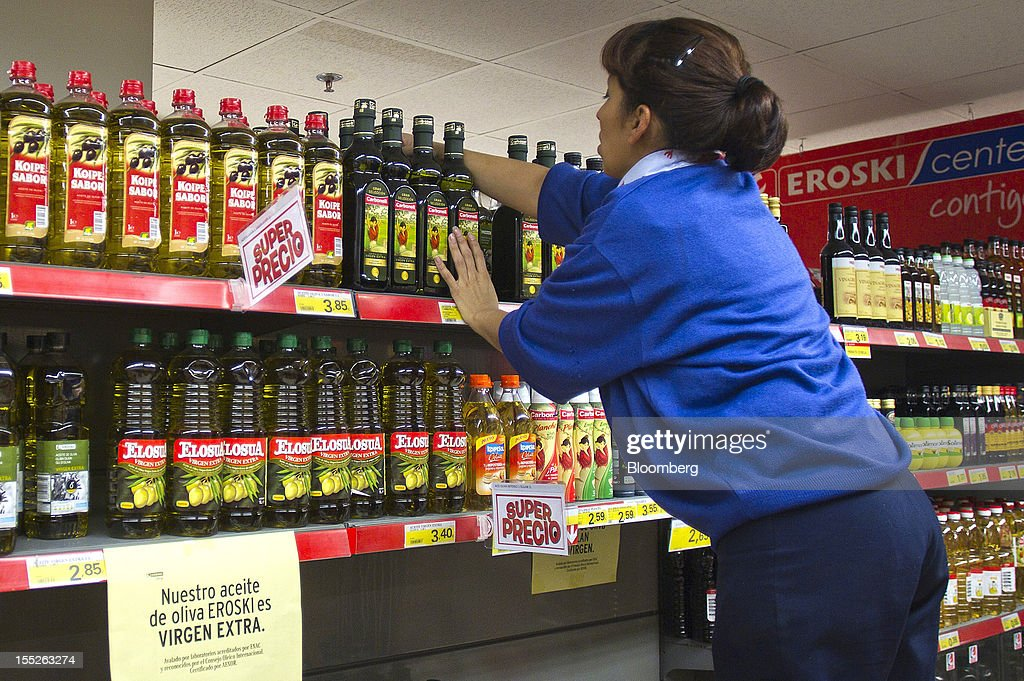 A worker re-stocks a shelf with bottles of Spanish olive oil at an Eroski Group supermarket in Madrid, Spain, on Friday, Nov. 2, 2012. Spain is unlikely to need a full bailout while any request from the euro area's fourth-largest economy for alternative support measures must be met with a swift response, Finnish Prime Minister Jyrki Katainen said. Photographer: Angel Navarrete/Bloomberg via Getty Images
