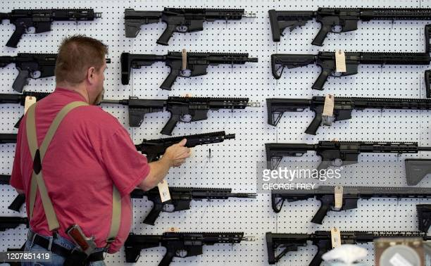 Worker restocks AR-15 guns at Davidson Defense in Orem, Utah on March 20, 2020. - Gun stores in the US are reporting a surge in sales of firearms as...