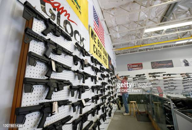 A worker restocks AR15 guns at Davidson Defense in Orem Utah on March 20 2020 Gun stores in the US are reporting a surge in sales of firearms as...