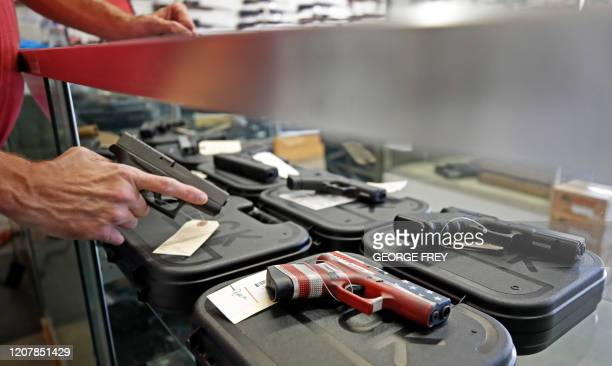 Worker restocks handguns at Davidson Defense in Orem, Utah on March 20, 2020. - Gun stores in the US are reporting a surge in sales of firearms as...