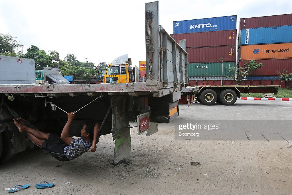 A worker rests in a hammock under a truck parked at a shipping container depot in Yangon, Myanmar, on Tuesday, Nov. 20, 2012. Myanmar's growth outlook has improved 'substantially' amid political reforms, which are expected to lead to a large influx of foreign investment, the Organization for Economic Cooperation and Development (OECD) said on Nov. 18. Photographer: Dario Pignatelli/Bloomberg via Getty Images
