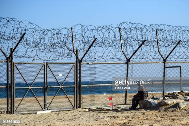 A worker rests on a rock next to a barbed wire fence running along a beach near the Korean Demilitarized Zone on February 3 2018 near Goseonggun...