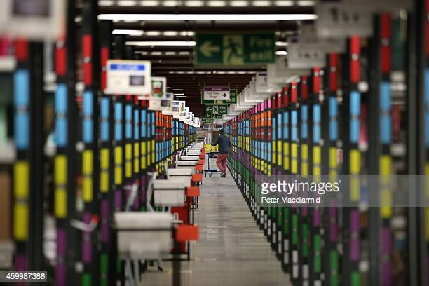 A worker retrieves goods from shelves at Amazon's warehouse on December 5 2014 in Hemel Hempstead England In the lead up to Christmas Amazon is...