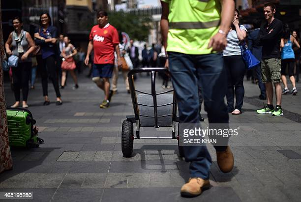 A worker returns back following a delivery in the central business district of Sydney on March 4 2015 Australia's economy remained soft in the fourth...