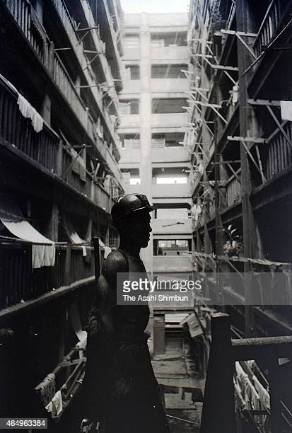 Worker returns to a dark concrete apartment at Hashima on August 12, 1956 in Takashima, Nagasaki, Japan. The coal mining island, is also known as the...