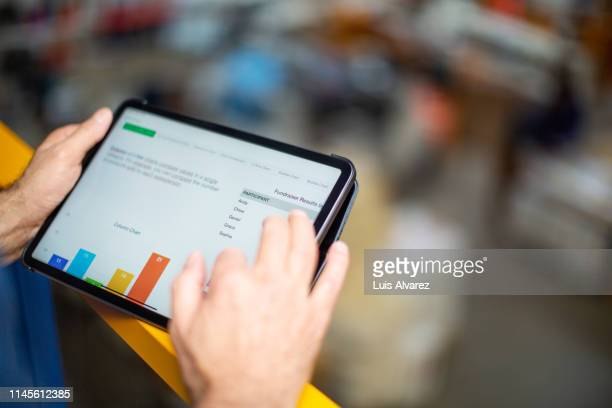 worker reviewing statistical graphs on tablet pc - part of stock pictures, royalty-free photos & images