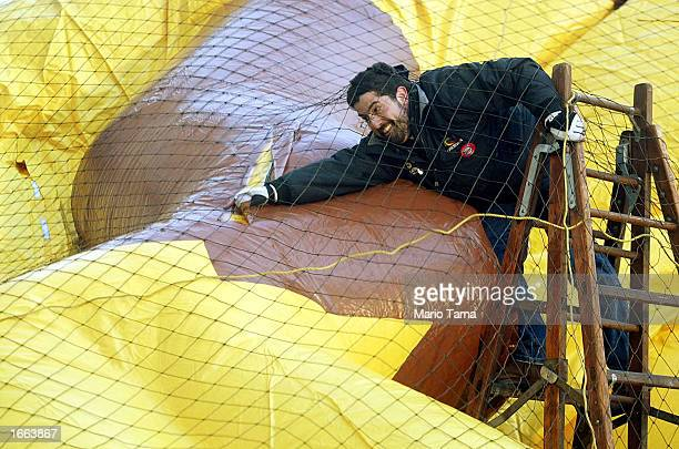Worker Rich Sasson helps inflate a giant helium balloon in preparation for the Macy's Thanksgiving Day Parade November 27, 2002 in New York City....