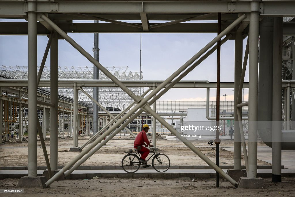 A worker rides a bicycle along a path the Sahiwal coal power plant owned by China`s stateowned Huaneng Shandong Rui Group in Sahiwal Punjab Pakistan..