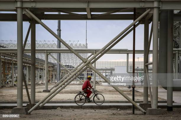 A worker rides a bicycle along a path the Sahiwal coal power plant owned by China's stateowned Huaneng Shandong Rui Group in Sahiwal Punjab Pakistan...