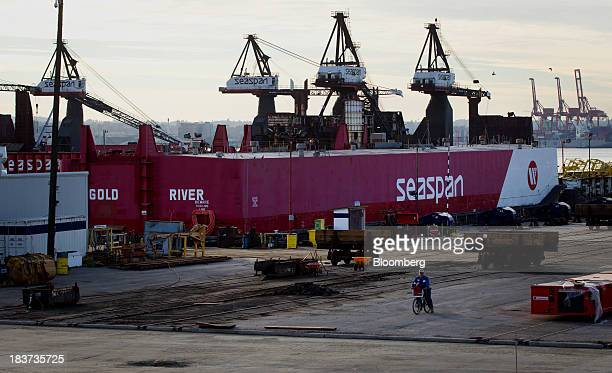 A worker rides a bicycle as the Gold River barge sits docked at the Seaspan Vancouver Shipyard in North Vancouver British Columbia Canada on...