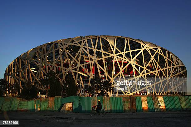 A worker rides a bicycle at sunset at the construction site of the National Stadium the main stadium of Beijing Olympic Games on January 3 2008 in...