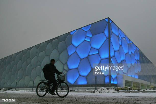 A worker rides a bicycle in the snow at the construction site of the National Aquatics Centre on January 17 2008 in Beijing China The centre built...