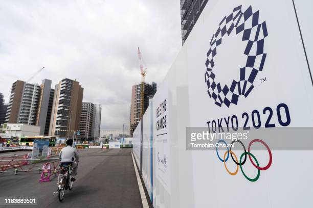 A worker rides a bicycle through the Olympic and Paralympic Village under construction on July 24 2019 in Tokyo Japan
