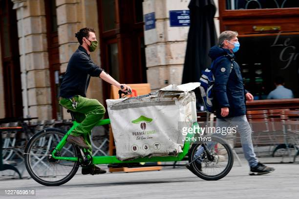 A worker rides a bike as he prepares to collect coffee grounds from a shop in Brussels on July 15 for the company Permafungi which recycles coffee...