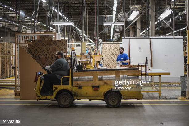 A worker rides a TaylorDunn Corp warehouse utility vehicle through the storage area of the Pella Corp manufacturing facility in Pella Iowa US on...