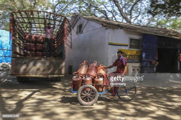 A worker rides a tricycle loaded with Hindustan Petroleum Corp liquefied petroleum gas cylinders at a depot operated by the company in Mumbai India...
