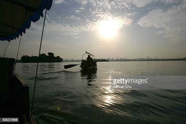A worker rides in his boat at the West Lake on June 4 2005 in Hangzhou Zhejiang Province of China The West Lake is one of China's most famous tourist...