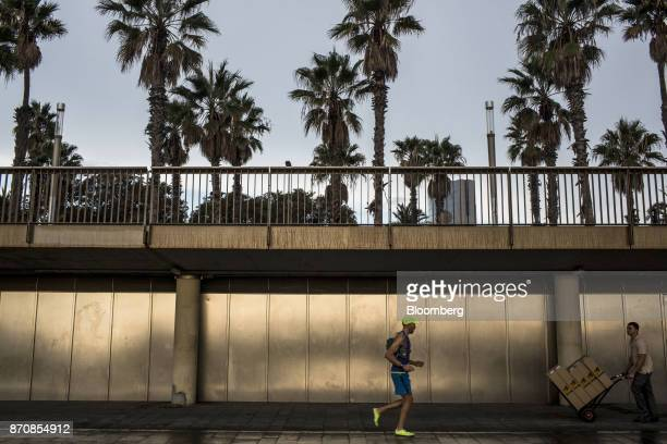 A worker right pushes a delivery trolley carrying boxes as a jogger runs by on Barceloneta beach in Barcelona Spain on Saturday Nov 4 2017 With...