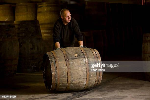 worker rolling whisky cask in whisky distillery - inverness scotland stock pictures, royalty-free photos & images