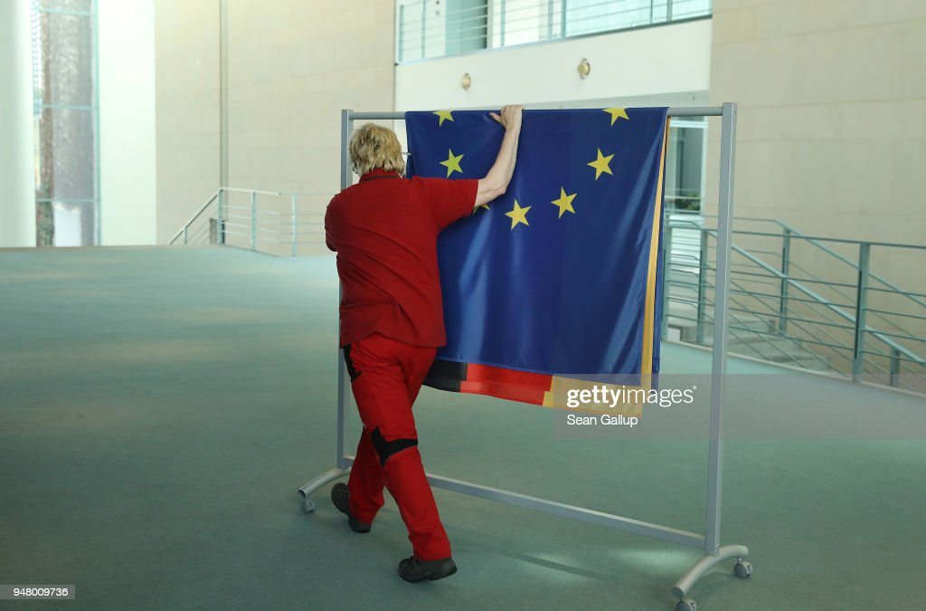 A worker rolls away flags, including those of Germany and the European Union, following the state visit of New Zealand Prime Minister Jacinda Ardern at the Chancellery on April 17, 2018 in Berlin, Germany. French President Emmanuel Macron, who is due to visit Berlin on April 19, gave an empassioned speech at the European Parliament yesterday, urging reforms to further behind the EU member states together and to counter authoritaianism.
