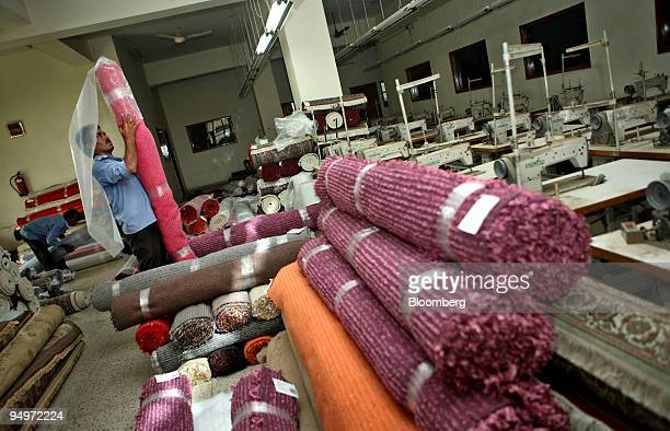 A worker rolls up carpets at an export house in Noida India on Tuesday Aug 25 2009 The worst global recession since the Great Depression has slashed...