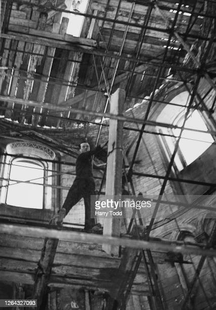 A worker roofing the tower of Temple Church with concrete slabs after German incendiary bombs had caused a fire which had left the building without a...