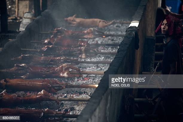 A worker rotates bambooskewered pigs over hot coals in Manila on December 24 2016 Lechon or roasted pig is a regular fare at Philippine festivities...
