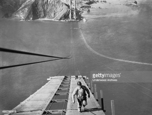 a worker running up one of the catwalks being built for the construction of the cable
