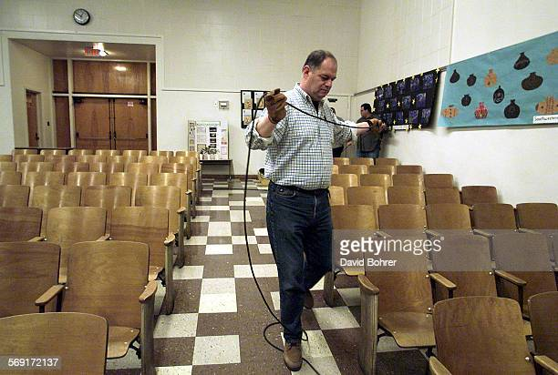 A worker runs cables for TV cameras Tuesday in the auditorium of Riverside Drive School in Sherman Oaks in advance of a scheduled off–site LAUSD...
