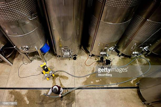 A worker runs hoses from a filtration system while filtering red wine from a fermenting tank at the Ferrante Winery in Geneva Ohio US on Friday Jan 4...