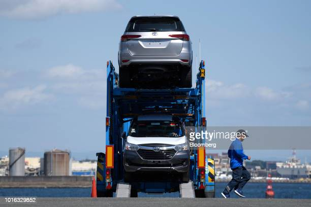 A worker runs past a car carrier trailer carrying Toyota Motor Corp vehicles at the Nagoya Port in Nagoya Japan on Tuesday July 31 2018 Japan is...