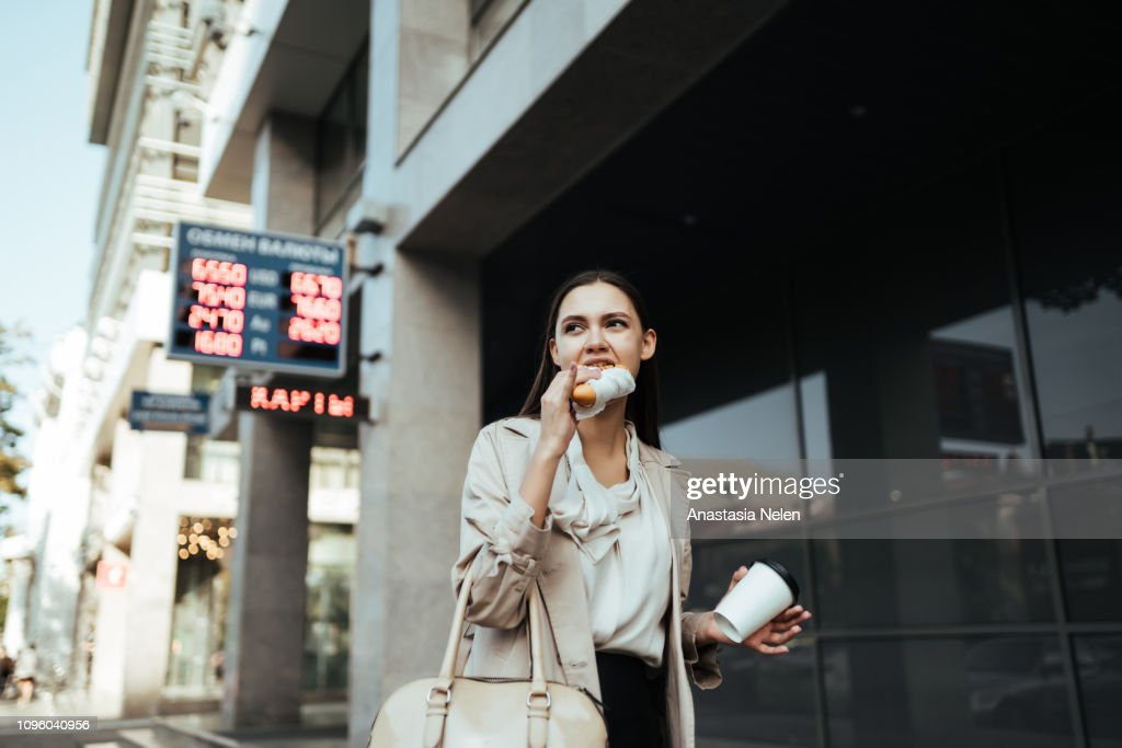 Worker rushes to work and eats on the go, drinks coffee in the street : Stock Photo