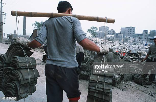 A worker salvaging tiles from the remnants of Fengdu an ancient city on the shores of the Yangtze River that is being dismantled to make way for the...