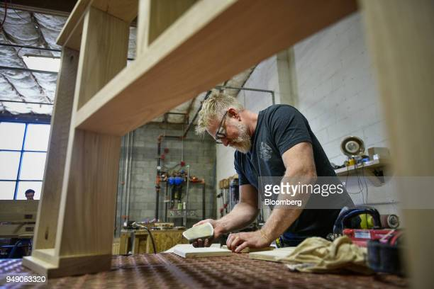A worker sands a piece of wood at the Old Wood Co sustainable furniture manufacturing facility in Asheville North Carolina US on Wednesday April 11...