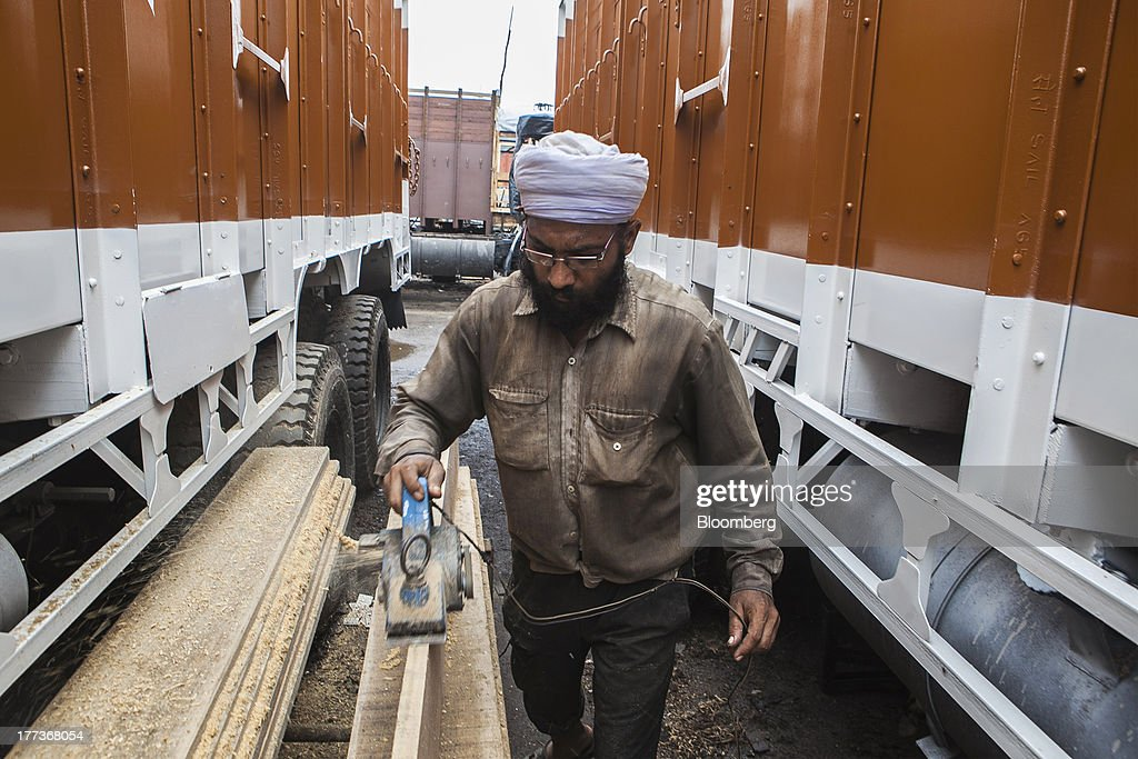 A worker sands a plank of wood between two trucks at the Sanjay Gandhi Transport Naga depot in New Delhi, India, on Thursday, Aug. 22, 2013. Indias rupee plunged 4.4 percent to a record this week in its worst performance since 1993 on signs the U.S. is getting closer to reducing stimulus that fueled demand for emerging-market assets. Photographer: Prashanth Vishwanathan/Bloomberg via Getty Images