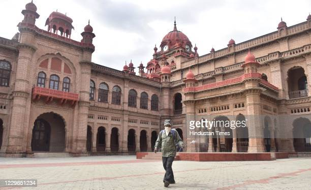 Worker sanitizes the campus at Khalsa College after the state government allowed reopening of colleges and universities that were closed due to the...