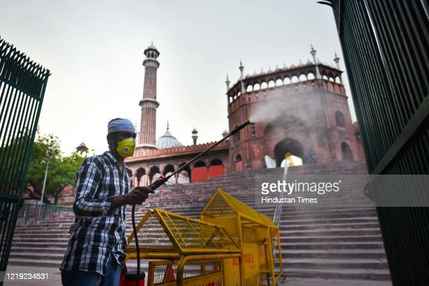 Worker sanitizing the area of the Jama Masjid complex with authorities comtemplating closing it to the public due to rising coronavirus cases on June...