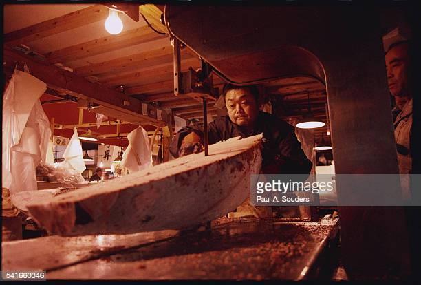 Worker Saws Tuna at Tsukiji Fish Market