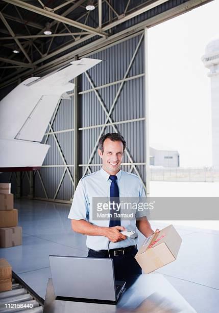 Worker scanning box in hangar