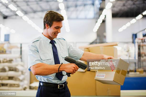 Worker scanning box in shipping area