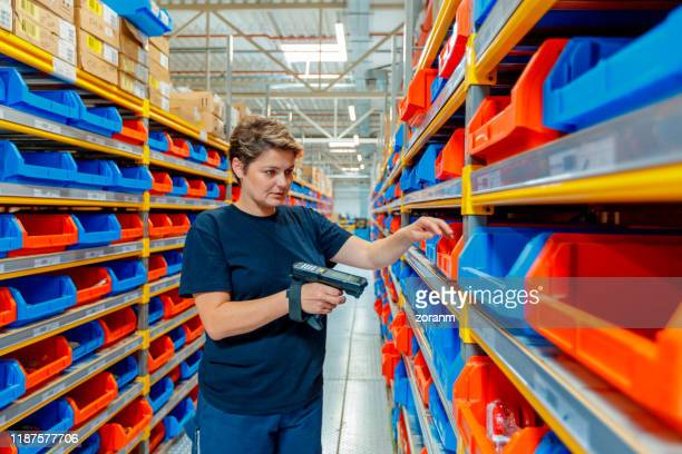 worker scanning boxes in distribution warehouse - industrial storage bins stock pictures, royalty-free photos & images