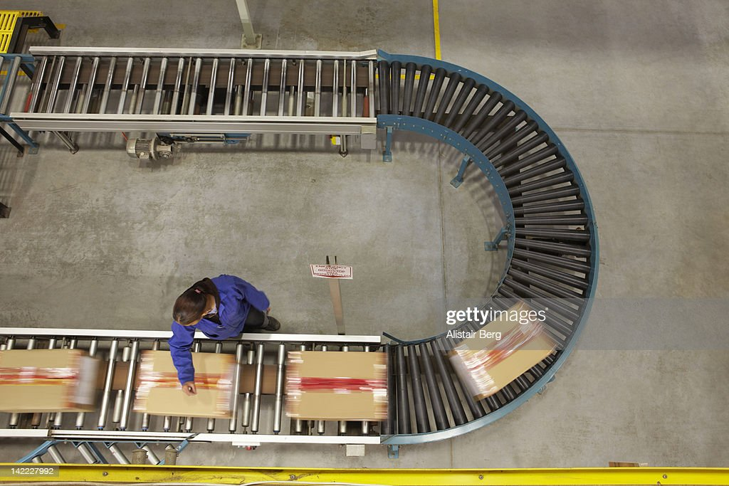 Worker scanning boxes on a conveyor belt : ストックフォト