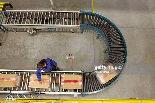 worker scanning boxes on a conveyor belt - heavy industry stock photos and pictures