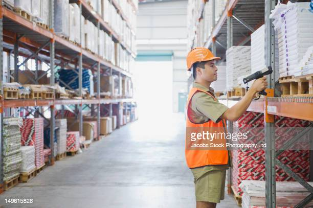 worker scanning inventory in warehouse - labeling - fotografias e filmes do acervo