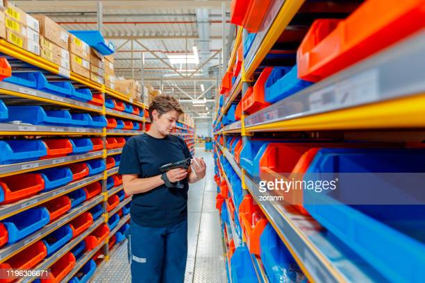 worker scanning items in distribution warehouse - industrial storage bins stock pictures, royalty-free photos & images