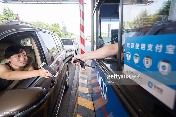 A worker scans a driver's smartphone to charge the highway toll by way of Alipay an online payment platform of Alibaba Group at Pengbu toll station...