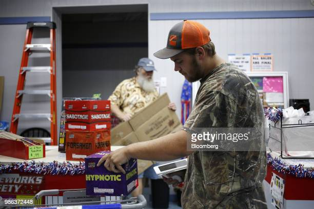 A worker scans purchases at the checkout counter of a fireworks store in Muldraugh Kentucky US on Wednesday June 27 2018 According to the American...