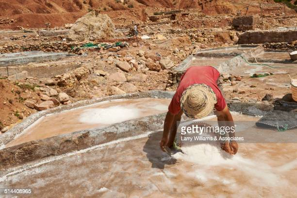 Worker scooping sand in quarry