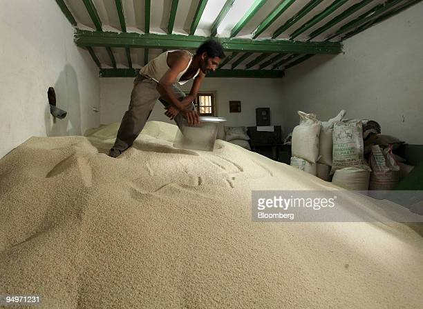 A worker scoops rice at a mill in Mandya India on Friday Aug 7 2009 This season a belowaverage monsoon the main source of irrigation may hinder...