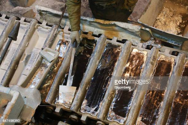 A worker scrapes off the top layer as molten aluminum cools in ingot moulds in the foundry at the Krasnoyarsk aluminum smelter operated by United Co...